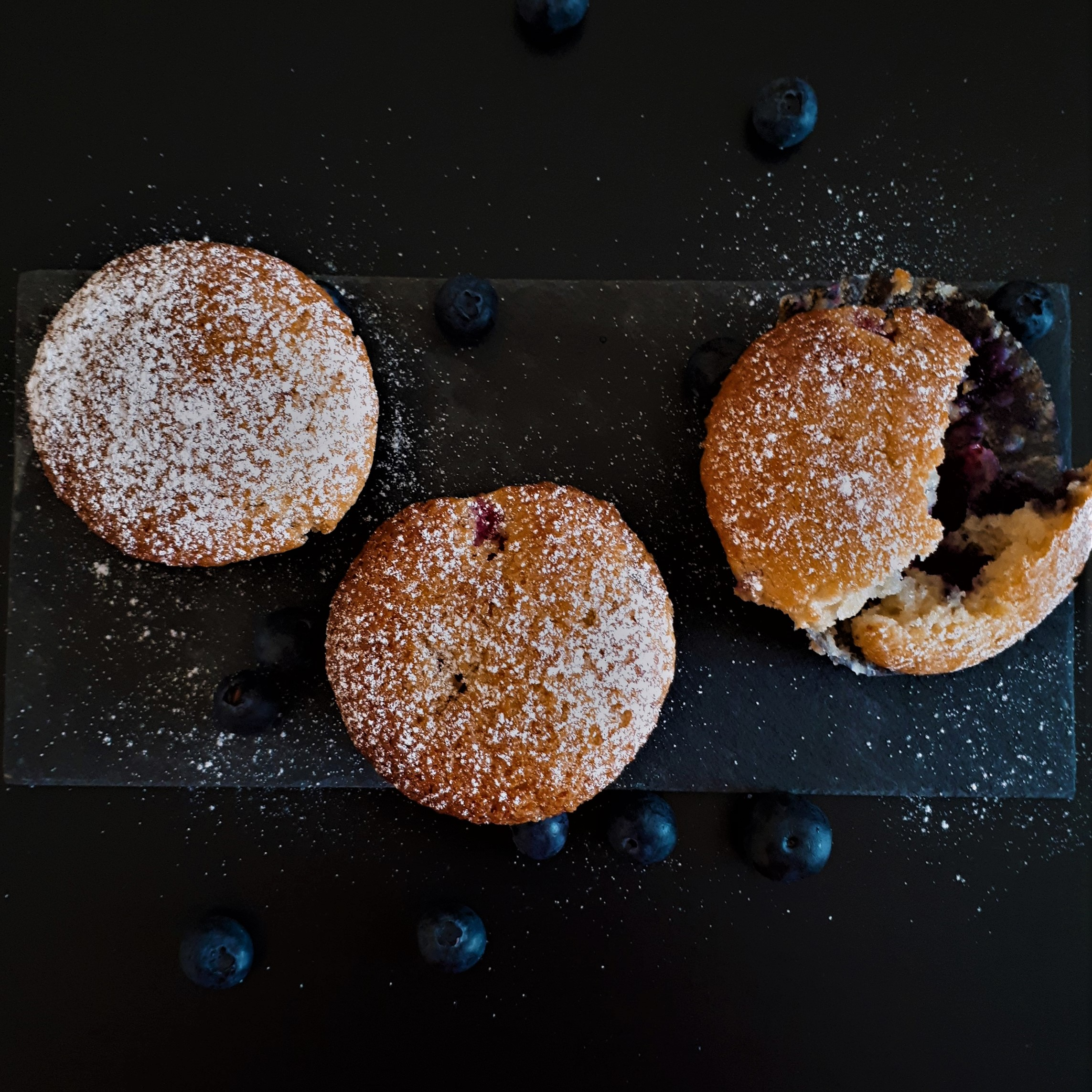 Pohľad zhora na čierny kamenný podnos na čiernom matnom podklade s troma muffinami posypanými príčkovým cukrom obsypané čerstvými čučoriedkami z jednej muffiny kúsok odtrhnutý s odhalenou náplňou z lesného ovocia.