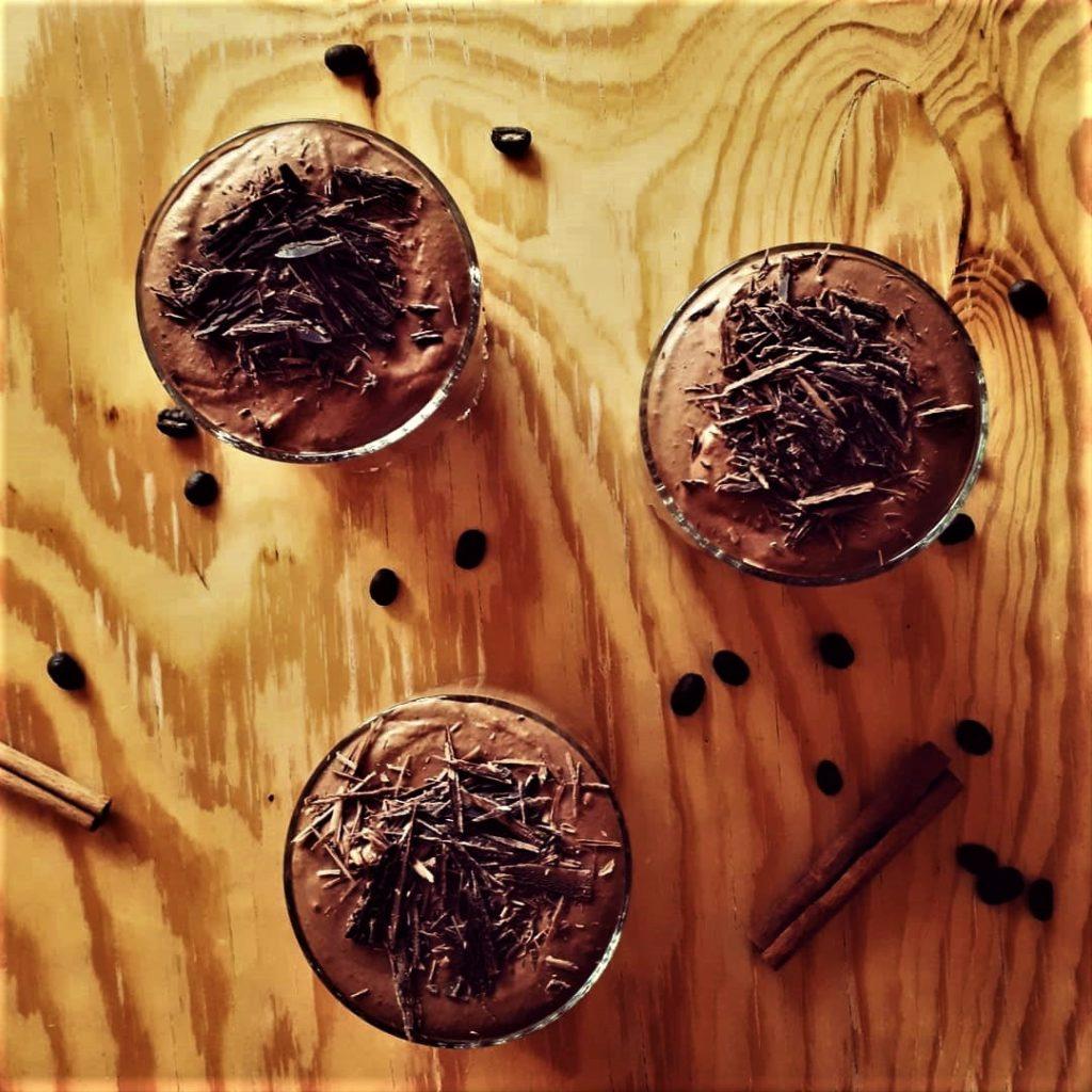 3 poháre gaštanovo-čokoládovej peny na drevenom stole dozdobené čokoládovými hoblinkami a obsypané kávovými zrnami a škoricou.