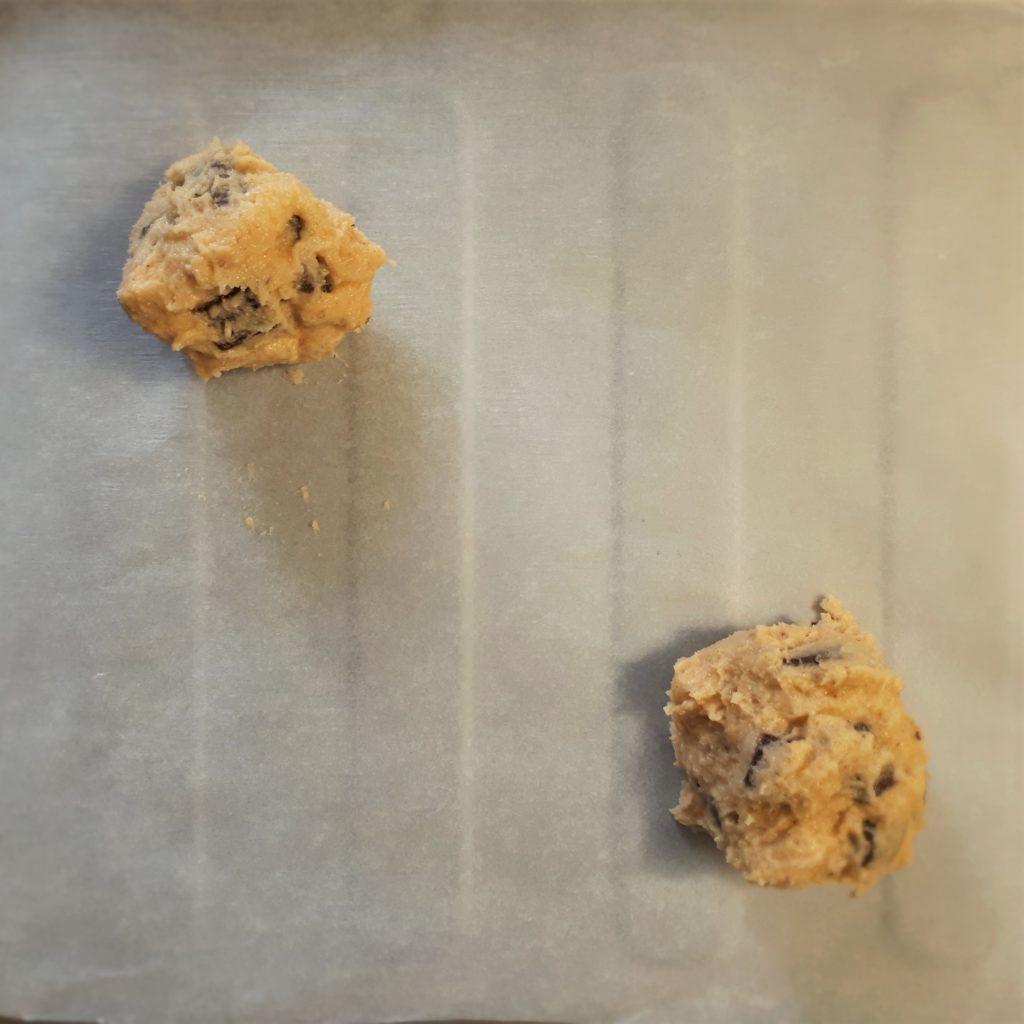 Dve kôpky zo sušienkového cesta na plechu s papierom na pečenie