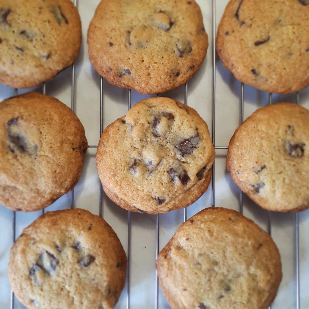 Osem upečených sušienok s kúskami horkej čokolády chladne na antikorovej mriežke