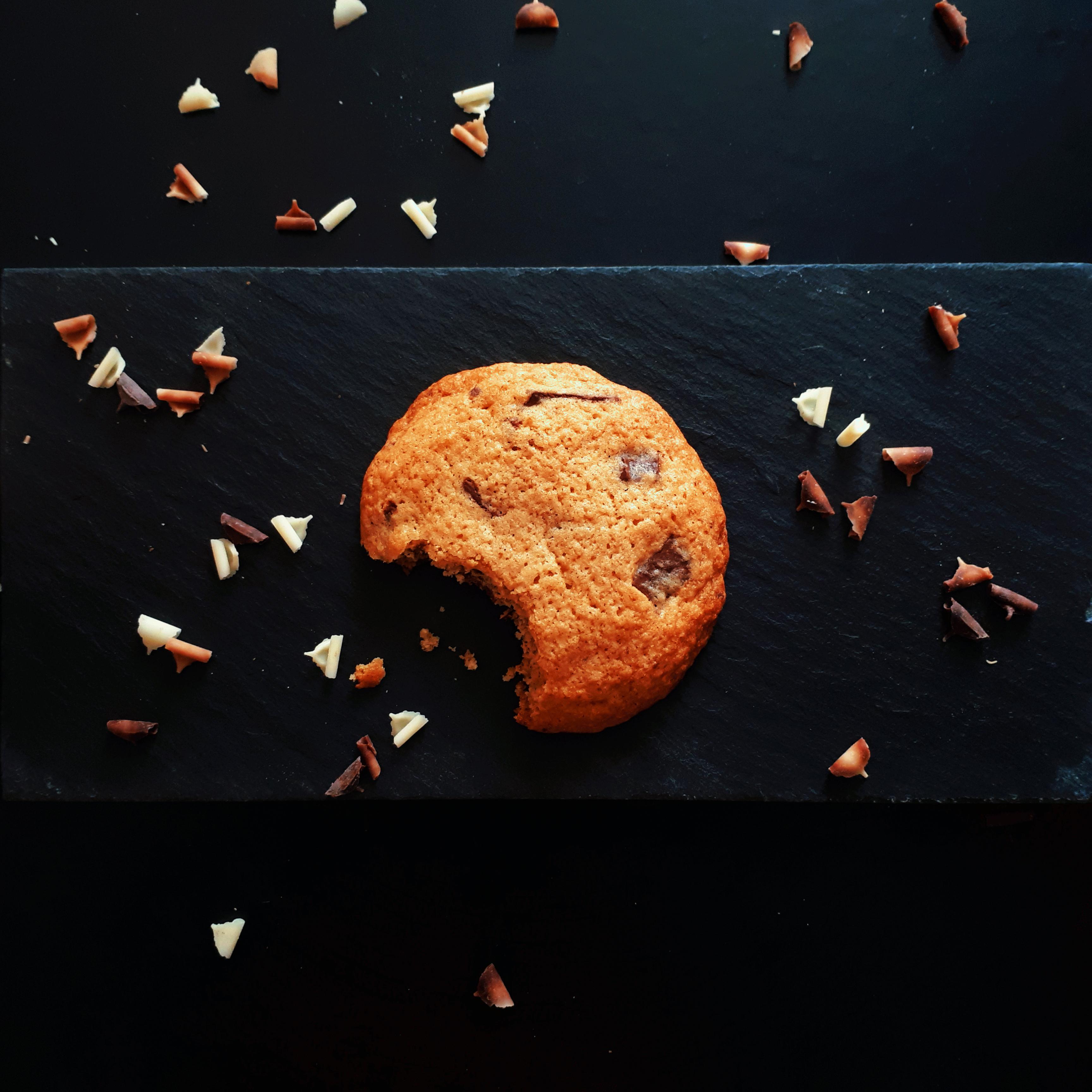 Pohľad zhora na čierny kamenný podnos na čiernom matnom podklade so sušienkou s kúskami horkej čokolády obsypané hoblinkami z bielej, mliečnej a horkej čokolády.