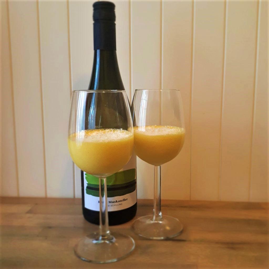 Dva vínové poháre so žltou vínnou penou posypanou strúhanou bielou čokoládou fľaša bieleho vína na drevenom stole drevená skrinka v pozadí