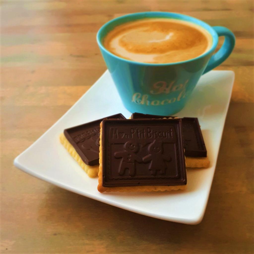 Biely obdĺžnikový tanier s troma maslovými sušienkami s horkou čokoládou modrý hrnček s kávou na drevenom stole