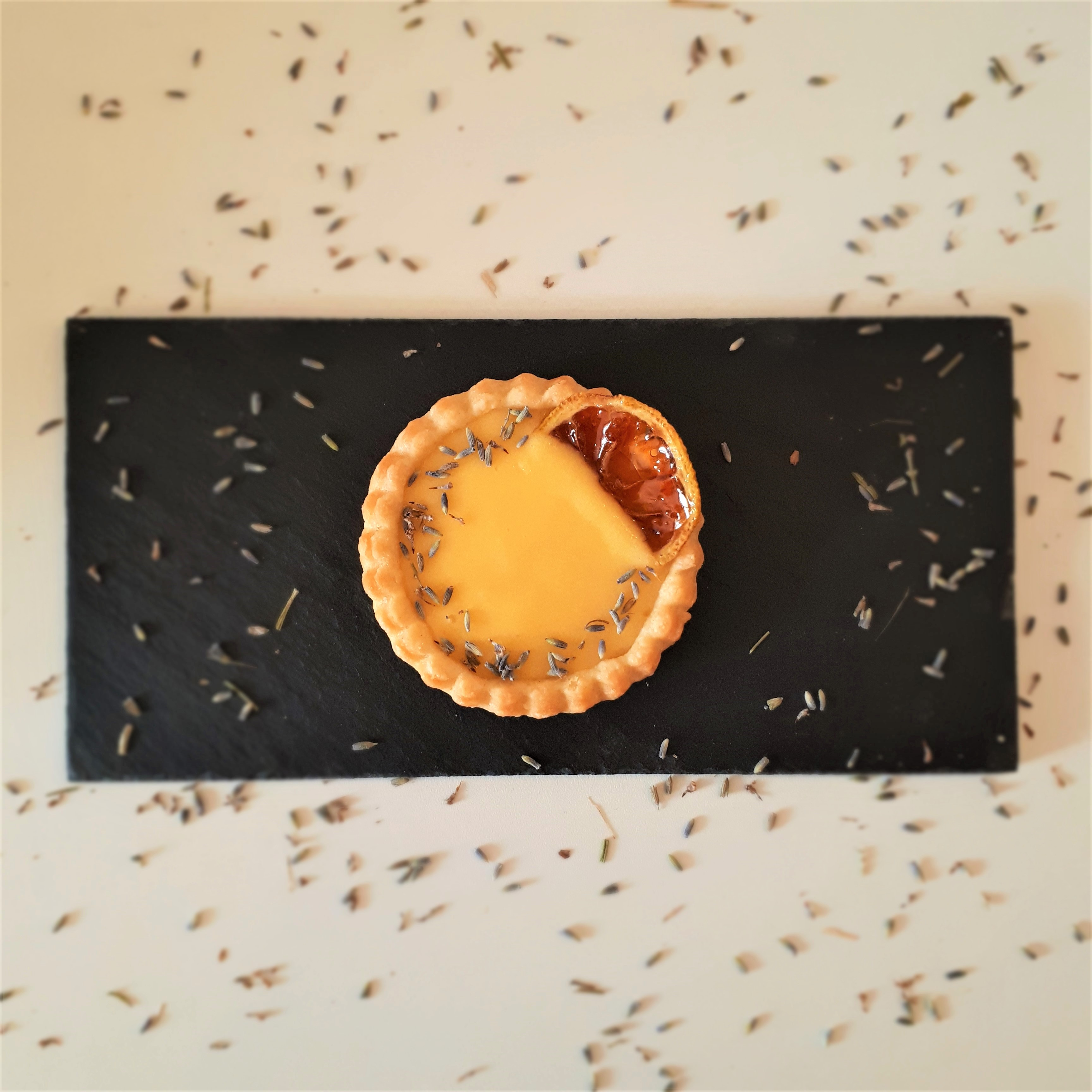 Tartaletka zo svetlého krehkého cesta naplnená citrónovým krémom lemon curd dozdobená plátkom karamelizovaného citróna a sušenou levanduľou na čiernej mramorovej doske na bielom povrchu