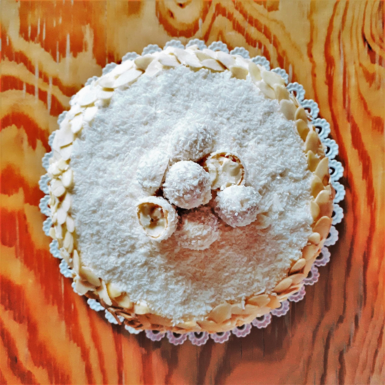 Raffaello torta s kokosom a plátkami mandlí navrchu Raffaello guľôčky na bielej tortovej podložke drevenom stole