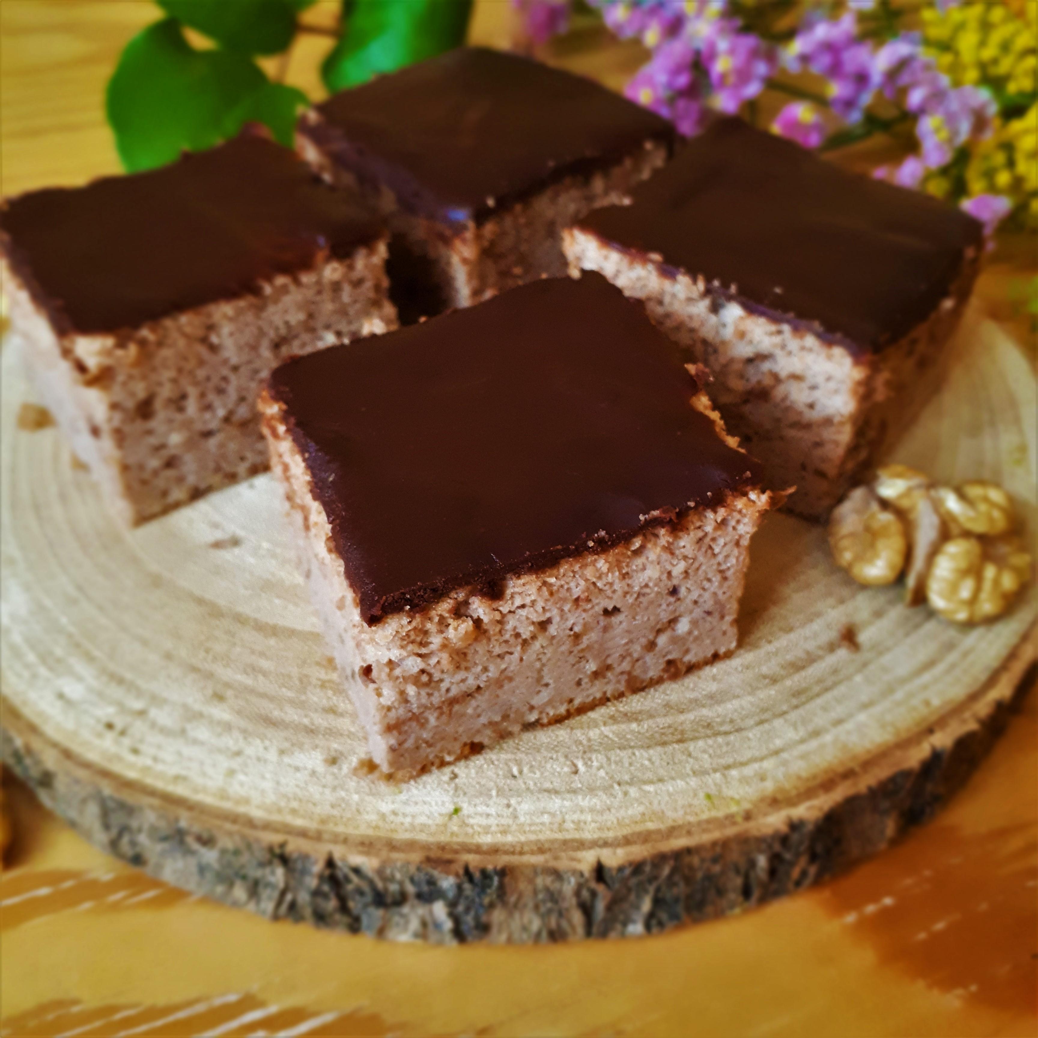 Štyri kocky gaštanového koláča s čokoládovou polevou na drevenej doske vlašský orech v pozadí lúčne kvety na drevenom stole