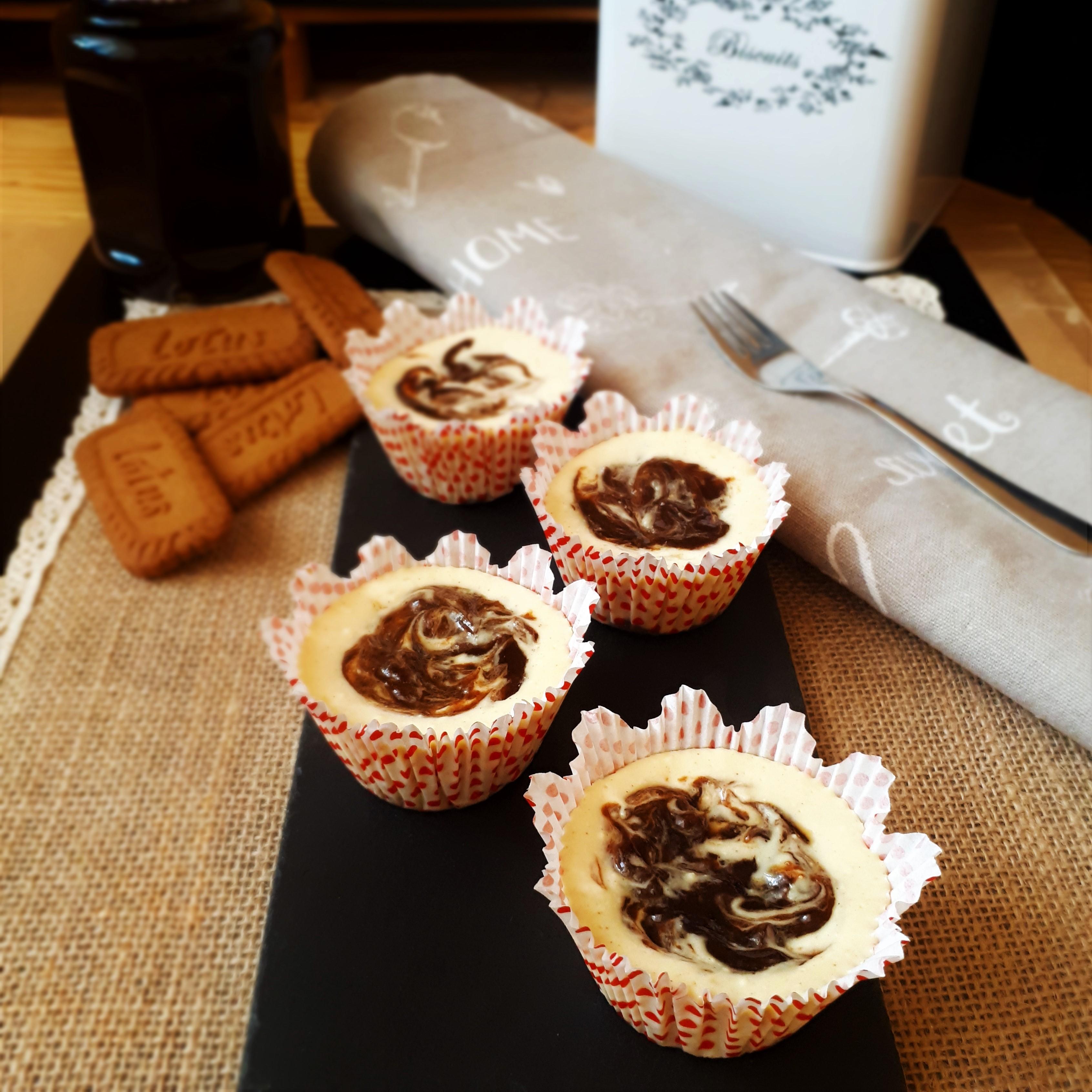 Štyri mini cheesecake muffiny so slivkovým lekvárom v bielych papierovým košíčkoch na čiernej kamennej doske plstenné prestieranie šedá kuchynská utierka s dezertovu lyžičkou vysypané Lotus sušienky pohároso slivkovým lekvárom biela dóza na sušienky
