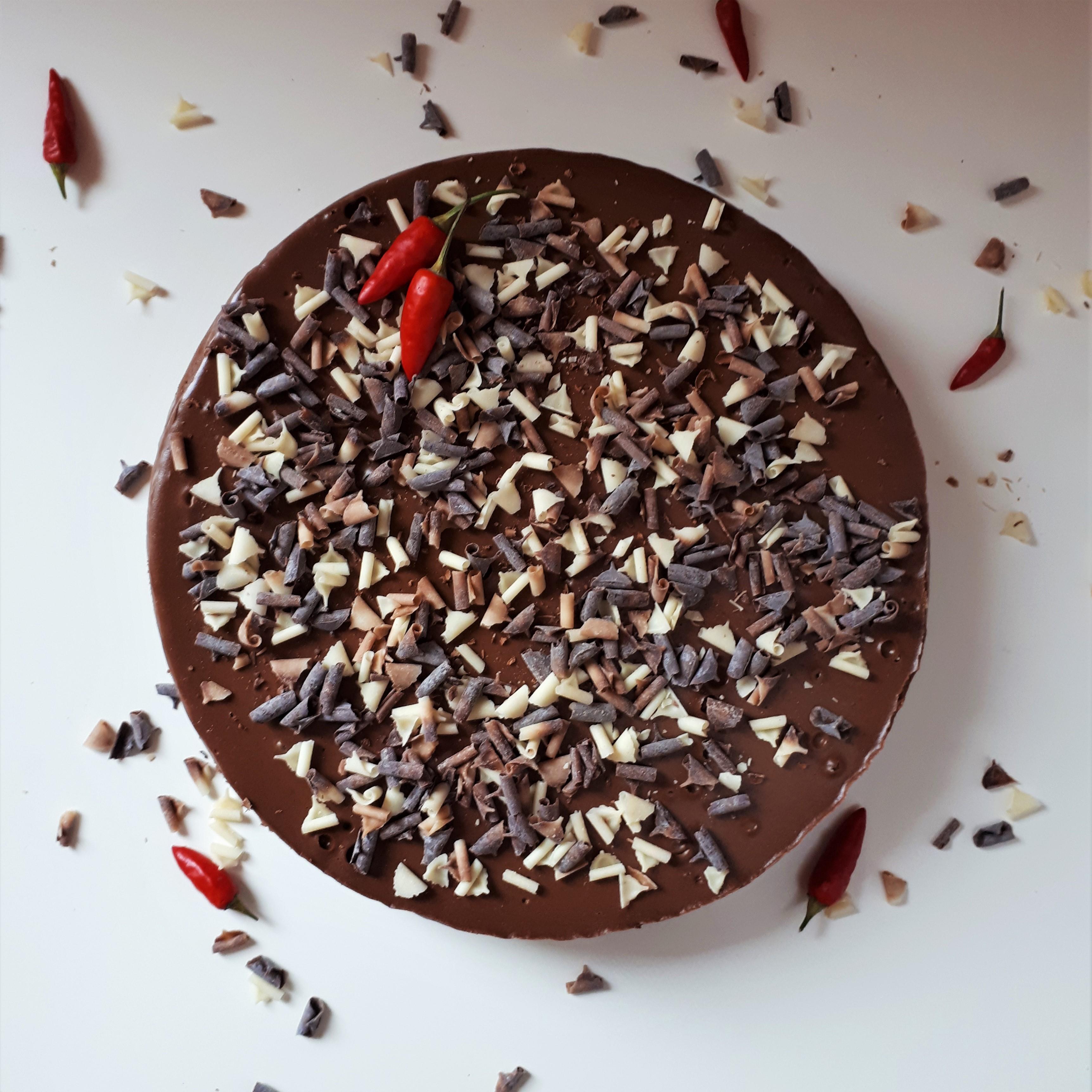 Čokoládový cheesecake s chilli posypaný čokoládovými hoblinkami z tmavej, mliečnej a bielej čokolády a dvoma chilli papričkami na bielom povrchu obsypaný čokoládovými hoblinkami a chilli