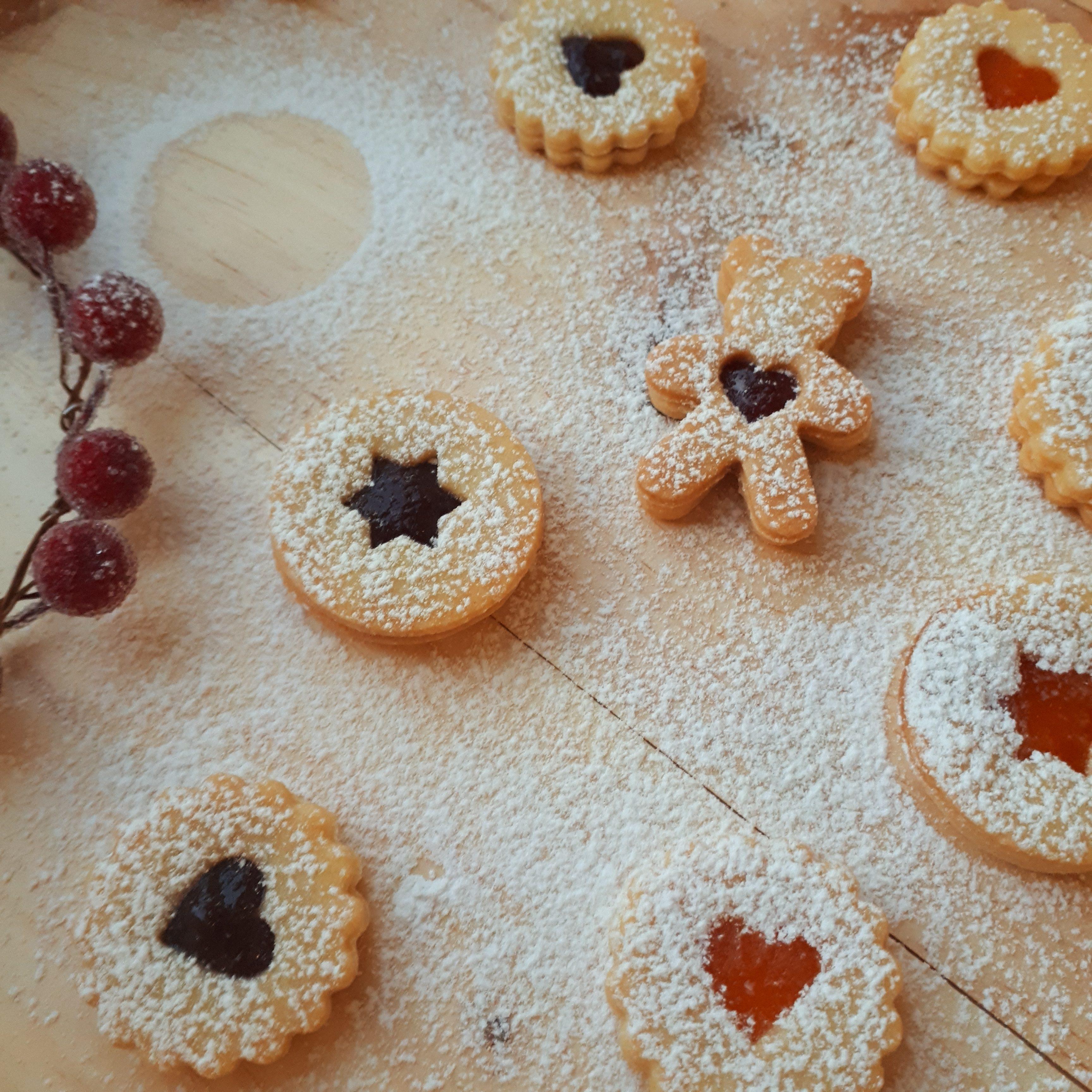 Linecké koláčiky v tvare koliesok a medvedíkov plnené jahodovým a marhuľovým džemom rozložené na drevenej doske posypané práškovým cukrom halúzka z brusníc