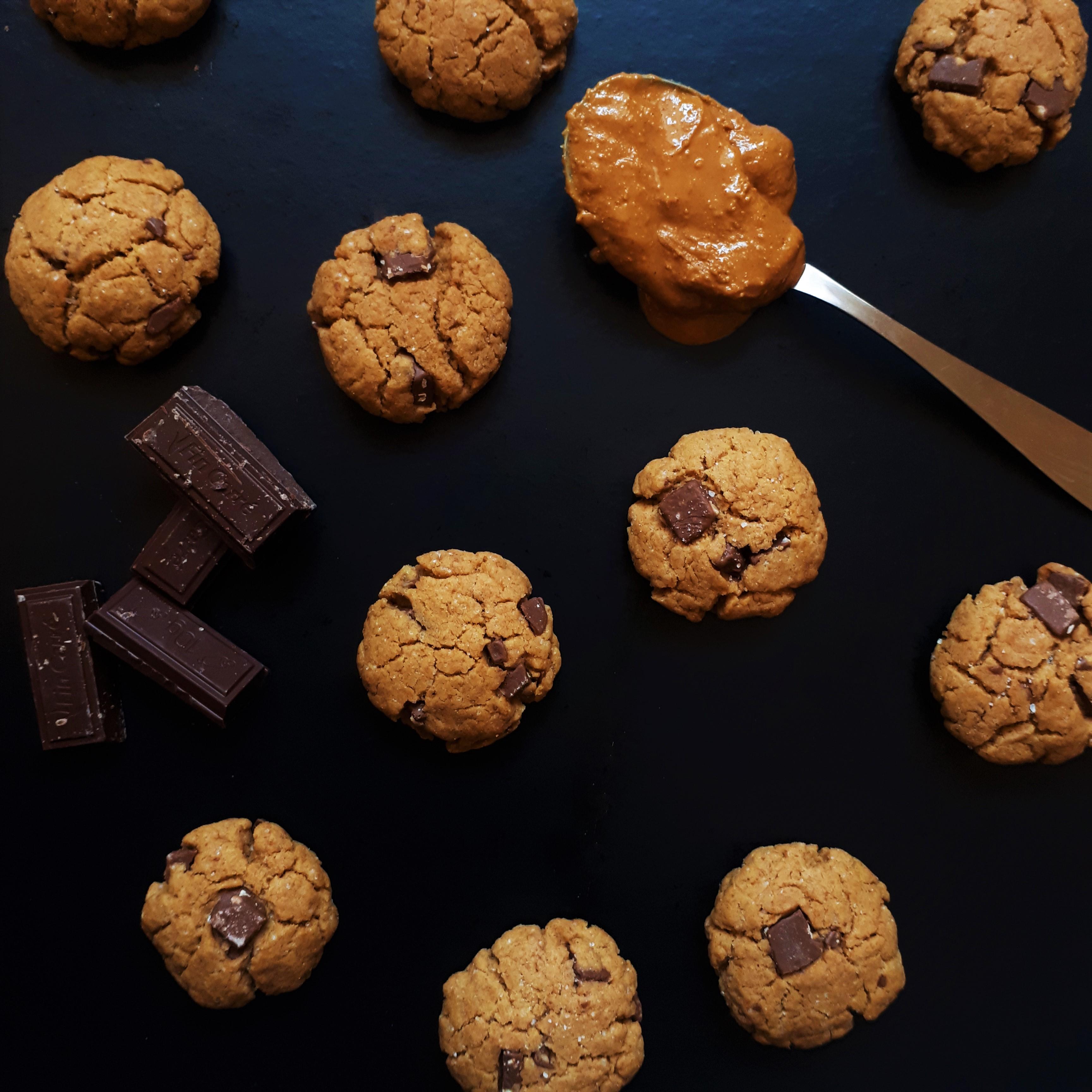 Rozožené sušienky z arašidového masla s kúskami čokolády na čiernom povrchu lyžica s arašidovým malsom a štyri kúsky horkej čokolády