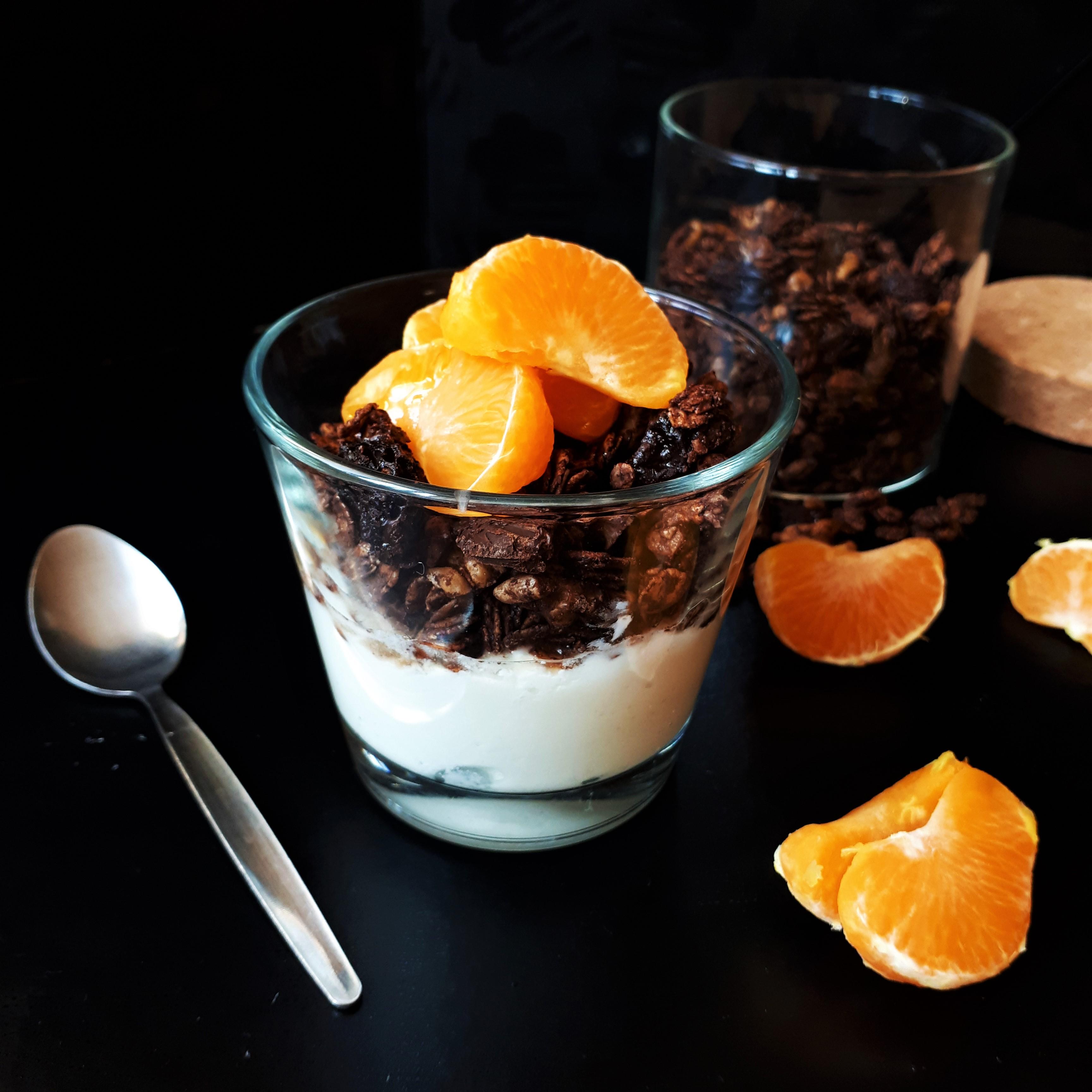 Pohár na dnes jogurt na ňom vrstva domácej čokoládovej granoly s hrozienkami a orechmi tri mesiačiky mandarinky poliate javorovým sirupom lyžička okolo mesiačiky mandarinky v pozadí sklenená dóza so zvyšnou granolou trochu rozsypanej granoly čierne pozadie
