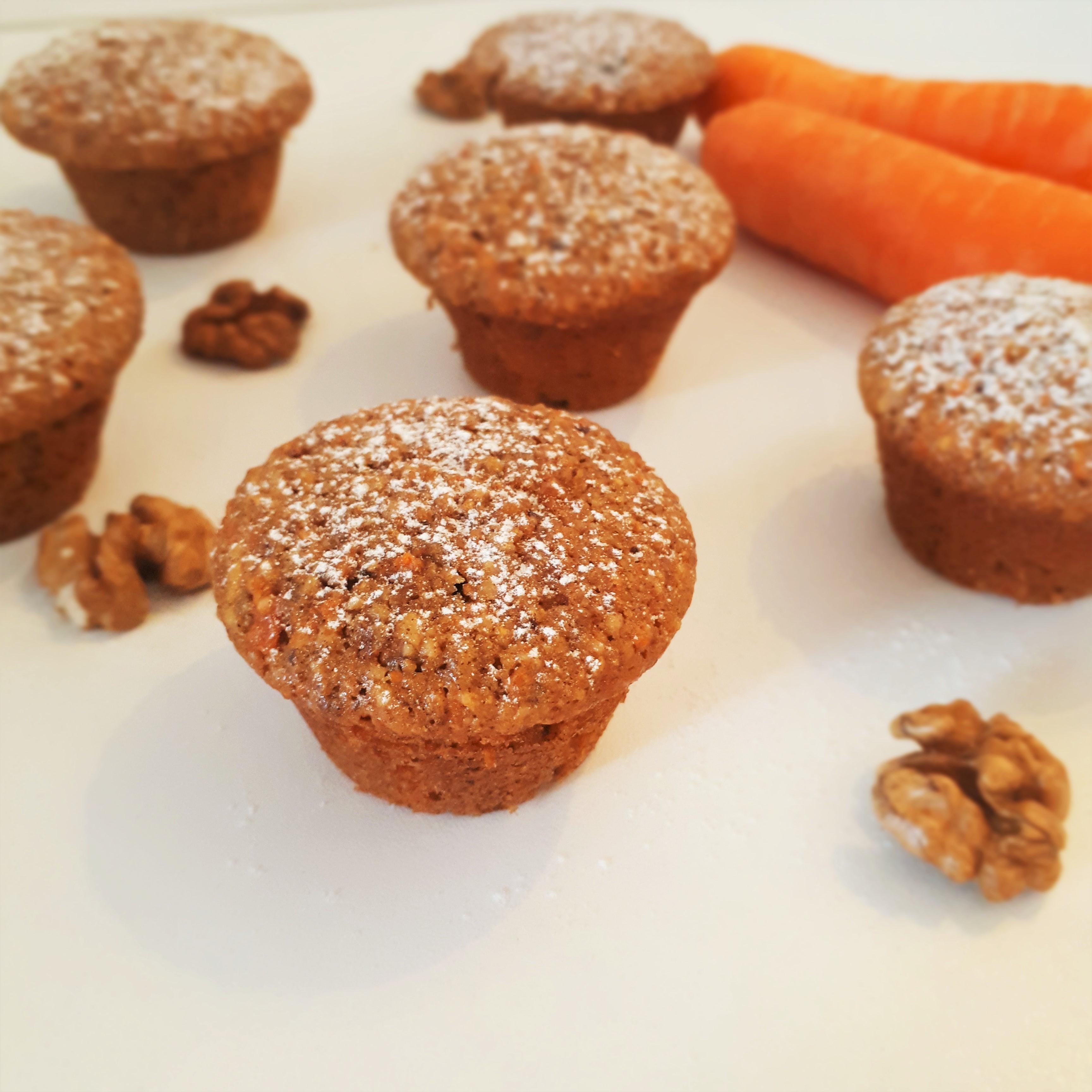 Šesť mrkovovo-orechových muffín posypaných práškovým cukrom na bielom povrchu okolo vysypané vlašské orechy vzadu dve mrkvy
