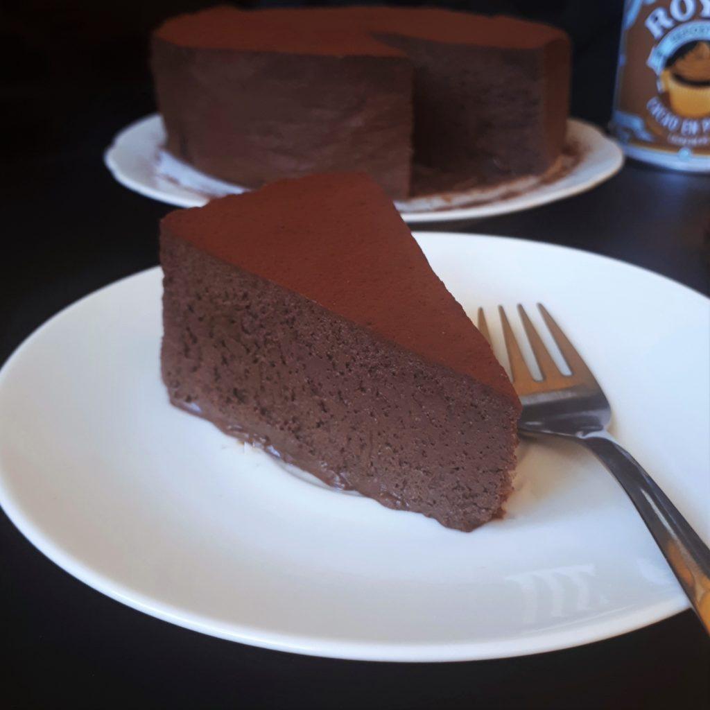 Kúsok penovej čokoládovej torty na bielom tanieri posypanej kakaom antikorová dezertná vidlička na čiernom povrchu v pozadí zvyšok torty na bielom tabnieri a dóza s kakaom