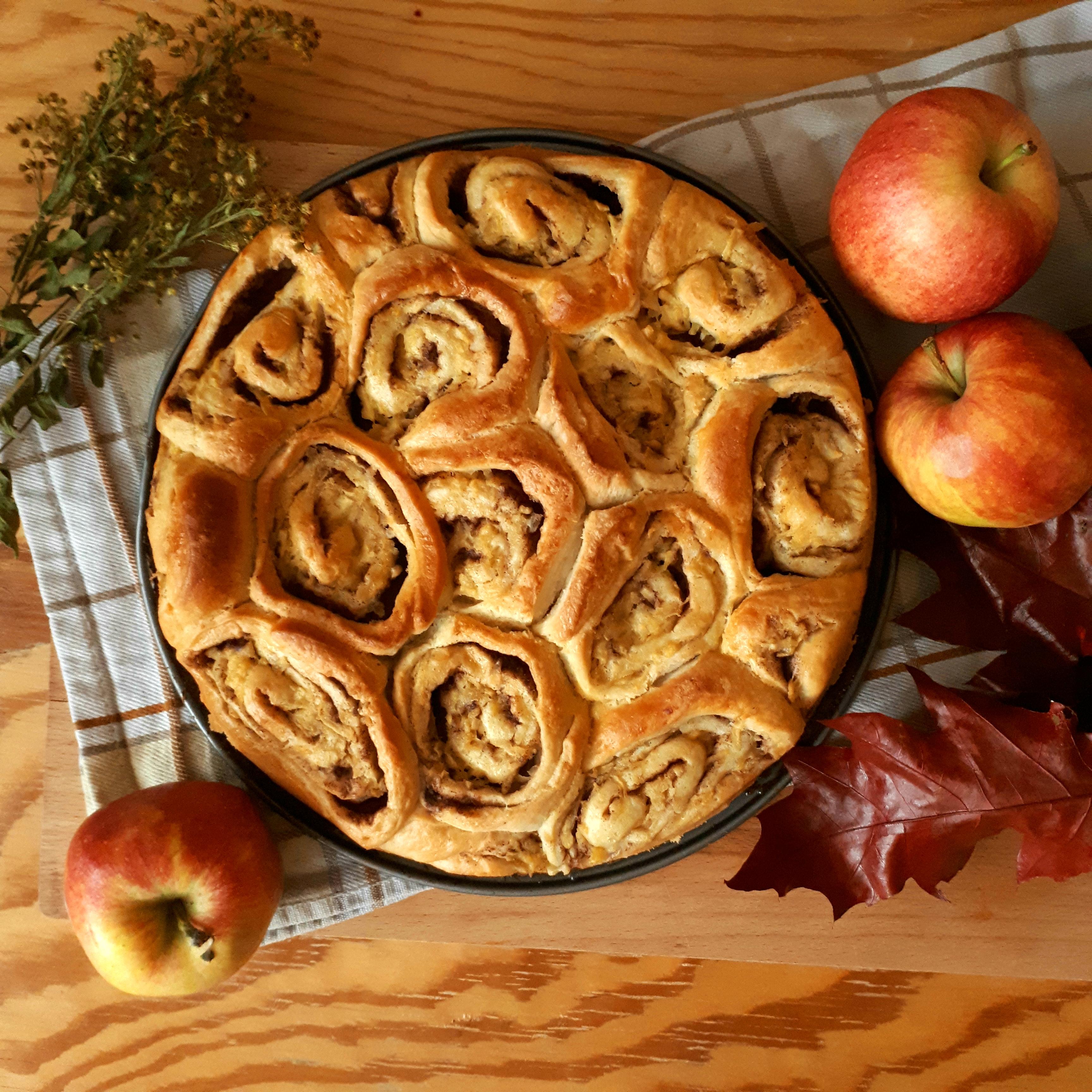 Okrúhla tortová forma s upečenými škoricovými slimákmi na drevenej doske žlto biela kuchynská utierka tri jablká usušená vetvička červené listy na drevenom stole