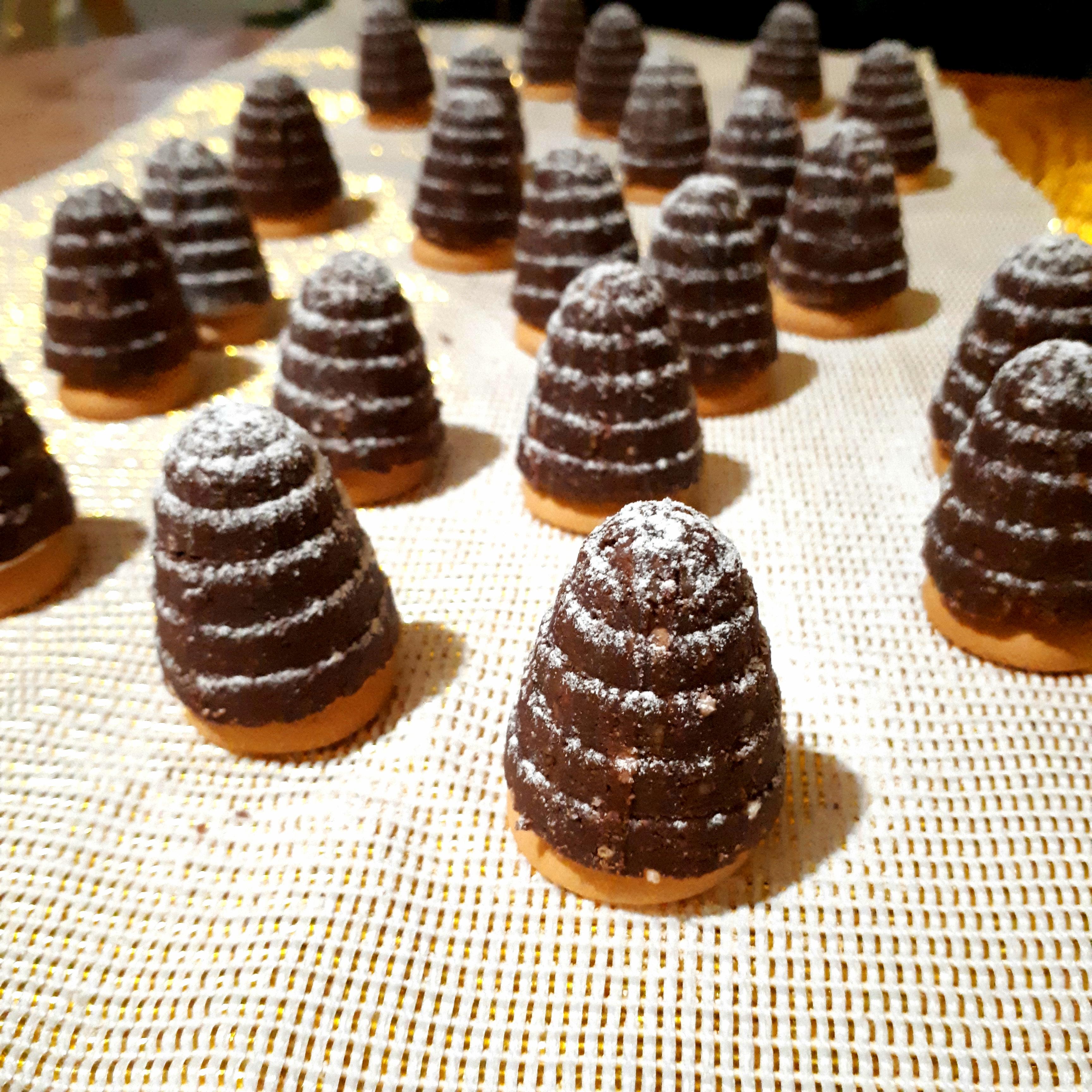 Hotové úliky z kakaového cesta na piškóte posypané práčkovým cukrom na zlatom obruse na drevenom stole v pozadí vianočný stromček