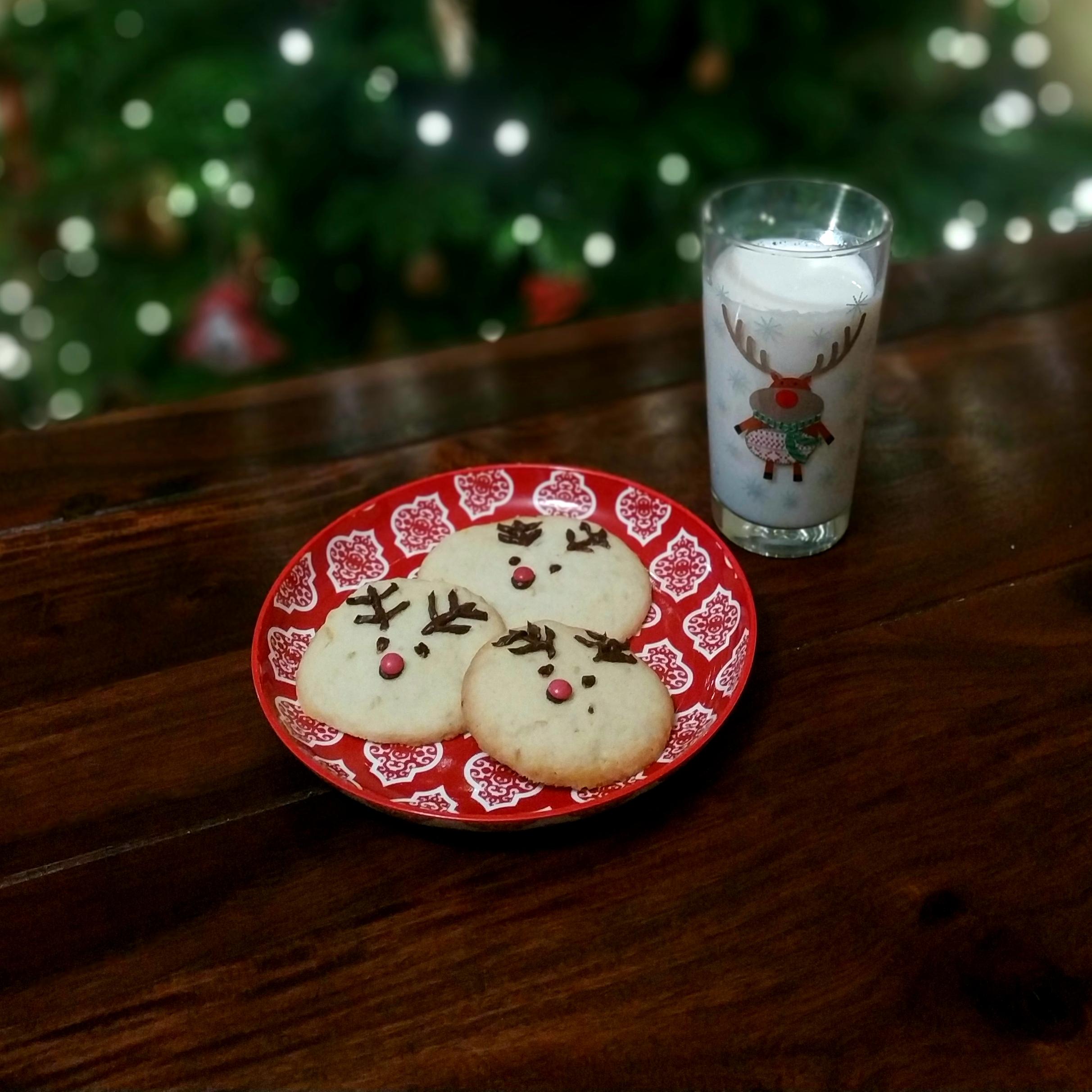 Tri sušienky sobíkovia na červenom tanieri na drevenom stole pohár s mliekom a motívom soba v pozadí vianočný stromček