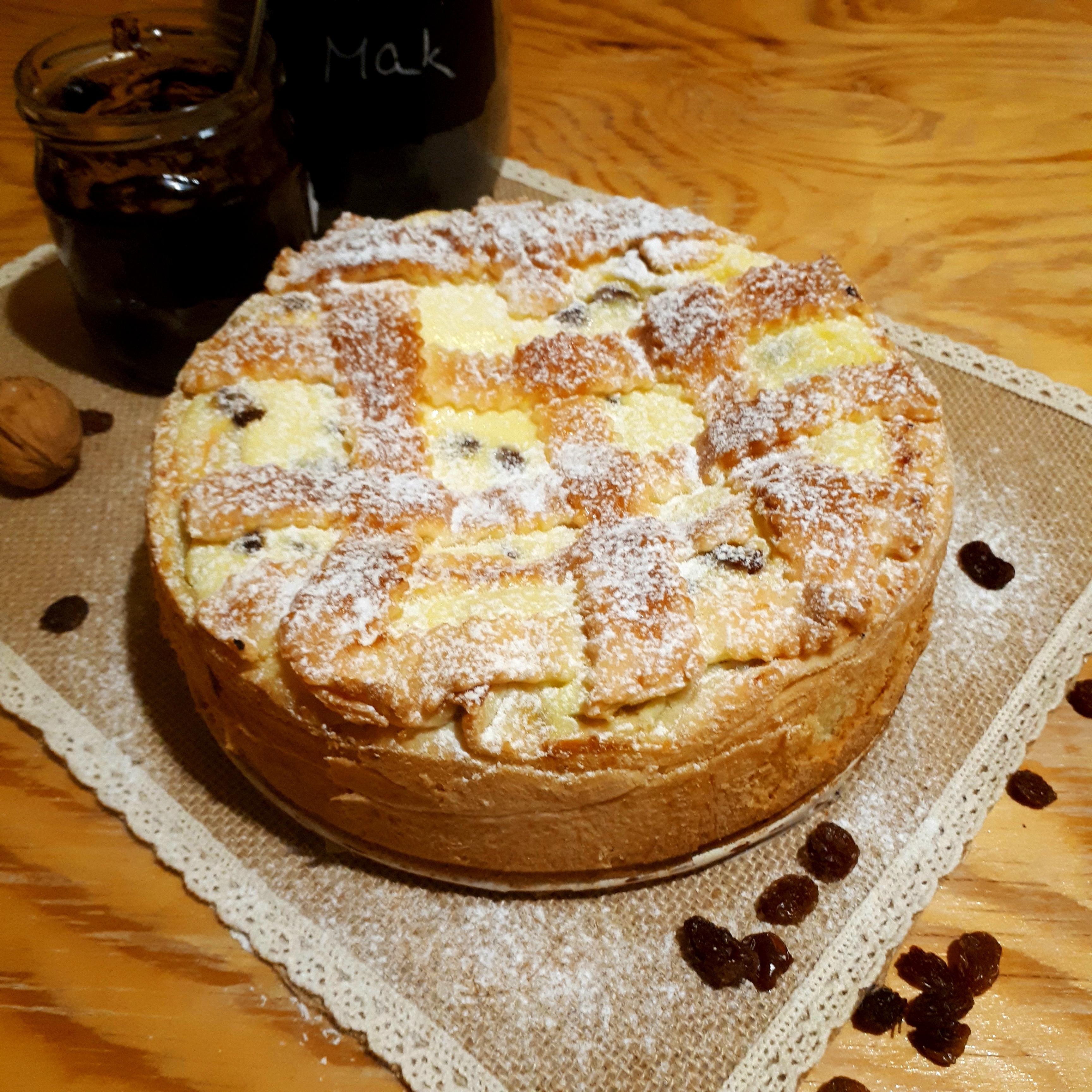Torta štedrák posypaná práškovým cukrom prírodné filcové prestieranie na drevenom stole okolo hrozienka vlašský orech v pozadí dóza so slivkovým lekvárom a lyžičkou a sklená dóza s makom