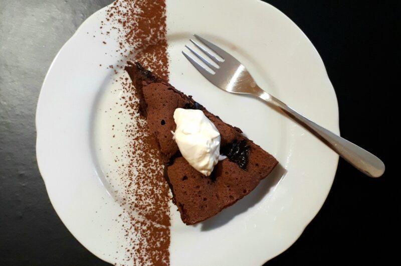 Kúsok čokoládového koláča so sušenými slivkami navrchu kopček kyslej smotany na bielom tanieri posypanom kakaom nerezová dezertná lyžička na čiernom povrchu